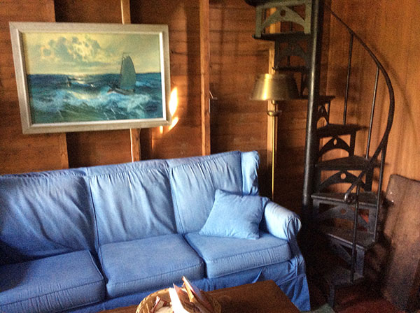 Blue couch opposite the library and next to the spiral staircase.